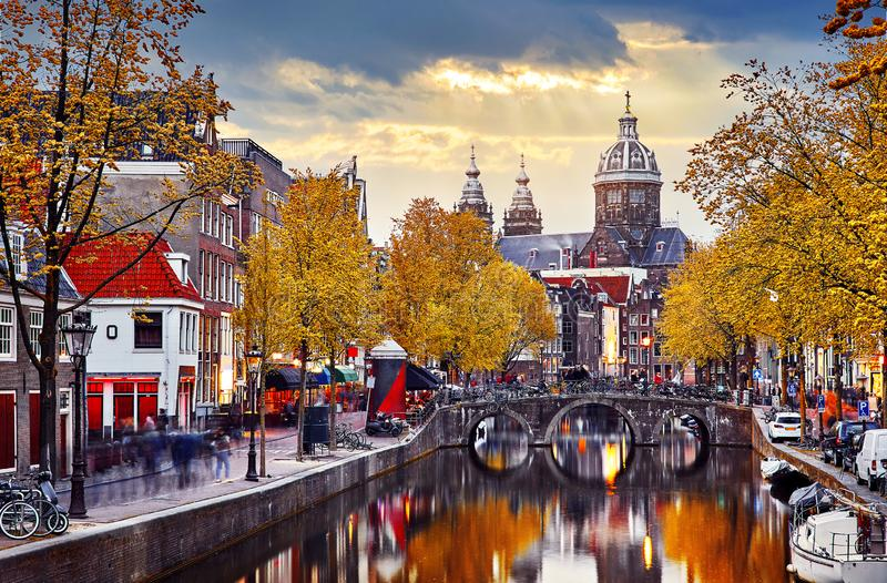 Amsterdam, Netherlands. Autumn sunset in Red-light district. View at Church saint Nicholas above bridge canal with boats. Embankment street lamp and yellow stock photography