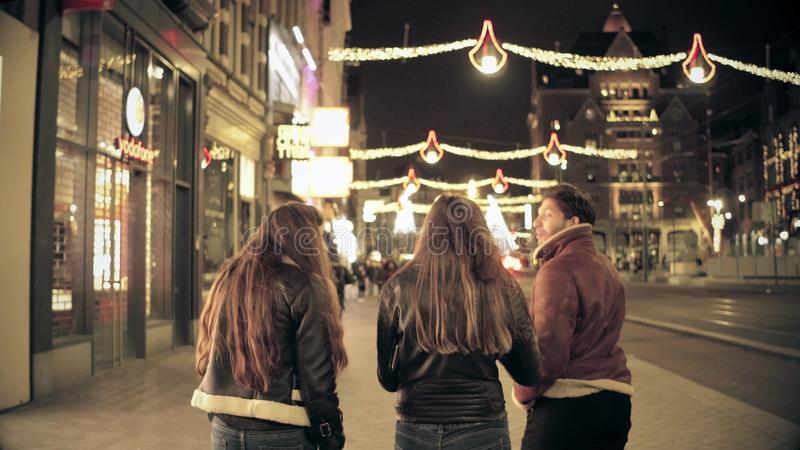 AMSTERDAM, NETHERLANDS - DECEMBER 25, 2017. Young people walk along city major street decorated for Christmas and New. AMSTERDAM, NETHERLANDS - DECEMBER 25, 2017 royalty free stock photos