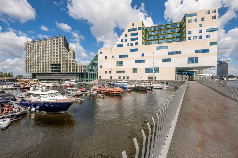 AMSTERDAM, the NETHERLANDS - JUL 03, 2016: Harbor with colorful boats in front of the modern office building for the court of just stock photo