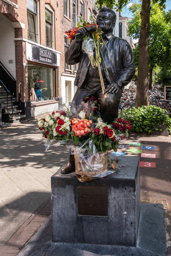André Hazes statue in Amsterdam, the Netherlands. Amsterdam, the Netherlands - July 1, 2019: André Hazes singer songwriter, bronze statue with bouquets of royalty free stock image
