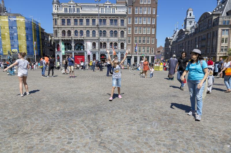 Children catch soap bubbles in the central Dam Square in Amsterdam stock image