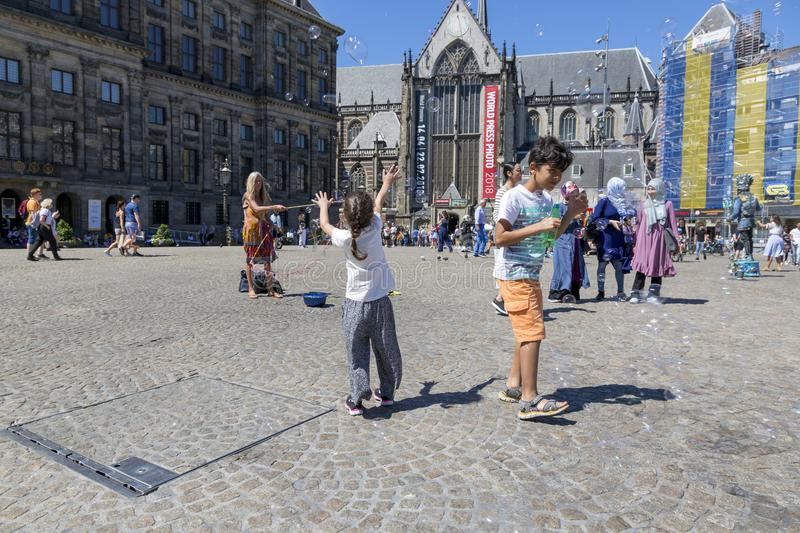 Children catch soap bubbles in the central Dam Square in Amsterdam stock photography