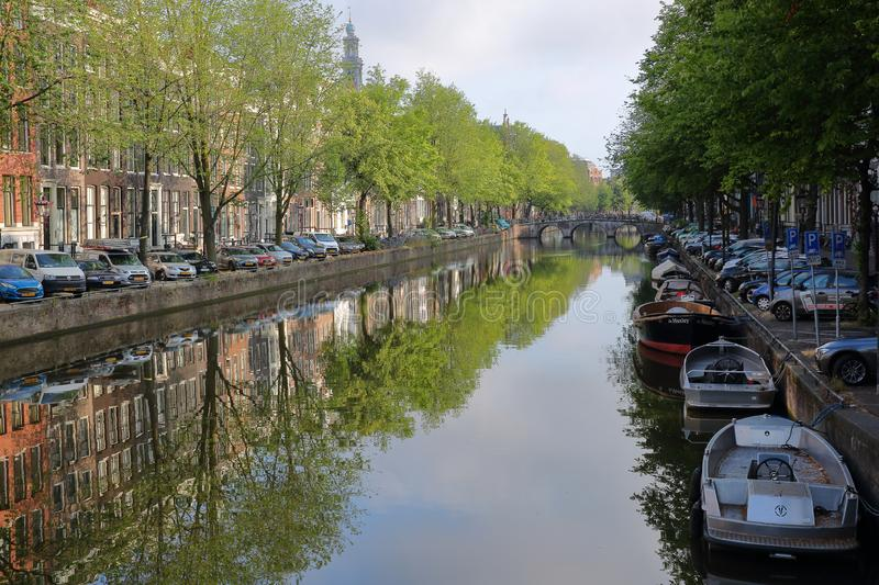 Crooked and colorful heritage buildings and boats, overlooking Herengracht canal with perfect reflections. AMSTERDAM, NETHERLANDS - JULY 17, 2019: Crooked and stock photos