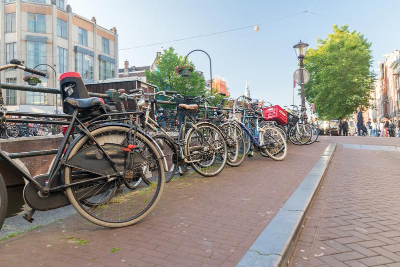 Bikes parked along the canal in Amsterdam`s historic district. Amsterdam, Netherlands - June 6, 2019: Bikes parked along the canal in Amsterdam`s historic stock image