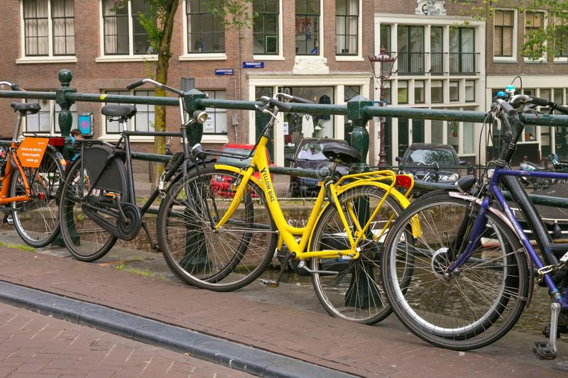AMSTERDAM, NETHERLANDS - JUNE 25, 2017: Different bicycles in Amsterdam near bridge fence in city center. stock photos