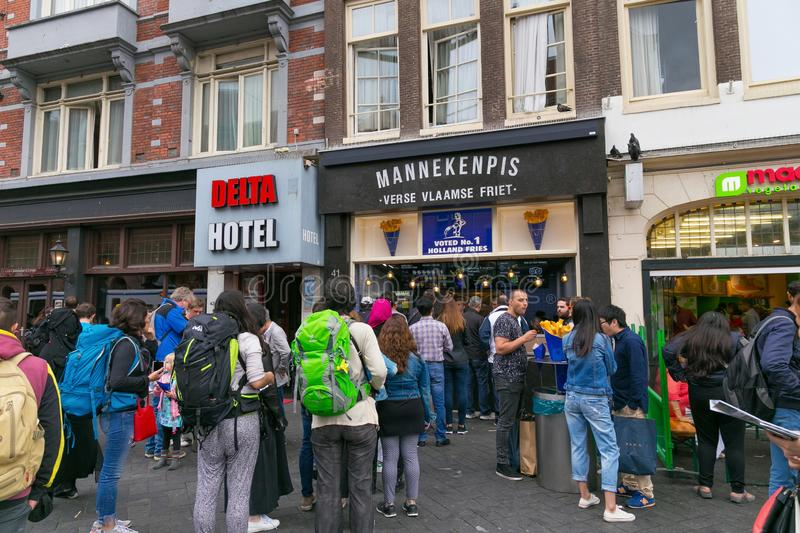 AMSTERDAM, NETHERLANDS - JUNE 25, 2017: Many tourists stand in line at one of the popular Mannekenpis Fries Shop. royalty free stock images