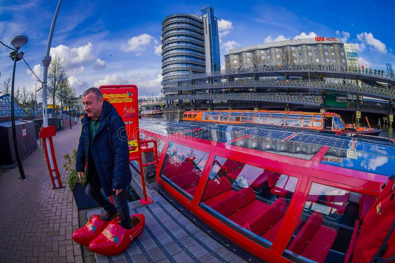 AMSTERDAM, NETHERLANDS, MARCH, 10 2018: Outdoor view of man wearing red huge shoes close to a red excursion boat or stock photos
