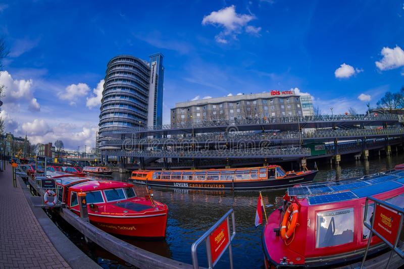 AMSTERDAM, NETHERLANDS, MARCH, 10 2018: Outdoor view of red excursion boat or cruise ship on Amsterdam water canal in stock image