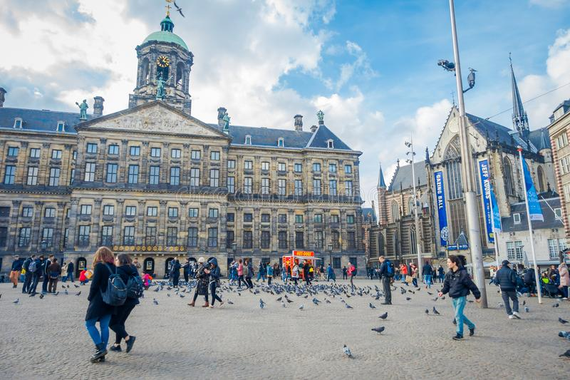 AMSTERDAM, NETHERLANDS, MARCH, 10 2018: Outdoor view of unidentified people walking at the Royal Palace on Dam Square in. Amsterdam. Built as city hall during royalty free stock photography