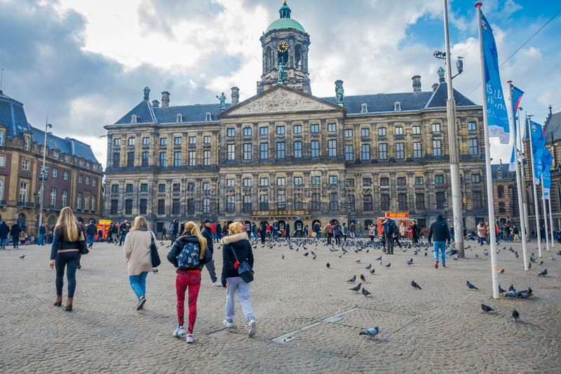 AMSTERDAM, NETHERLANDS, MARCH, 10 2018: Outdoor view of unidentified people walking at the Royal Palace on Dam Square in. Amsterdam. Built as city hall during royalty free stock photo