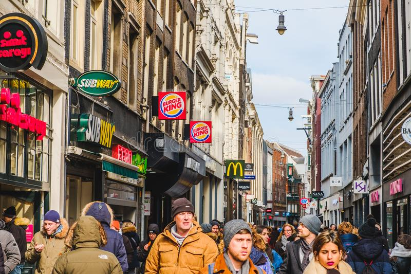 People walking on crowded street in Amsterdam city center on a s. Amsterdam, Netherlands - march 2018: People walking on crowded street in Amsterdam city center royalty free stock photo