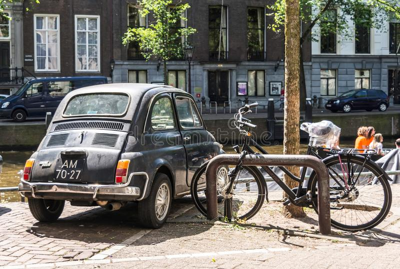 Amsterdam, Netherlands - May 21, 2018: Back of the black old rusty Italian small car Fiat 500L or Lusso parked at one royalty free stock image
