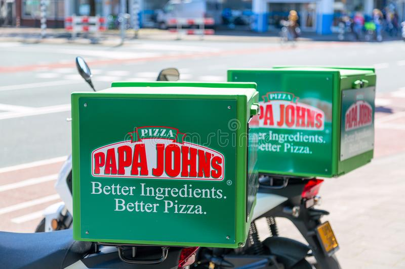 Amsterdam, Netherlands - May, 2018: A close-up of the Papa Johns Pizza logo on delivery bicycles outdoors. Papa John`s Pizza is a royalty free stock photography