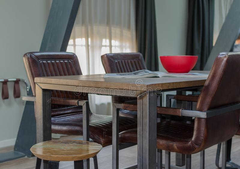AMSTERDAM, NETHERLANDS - May  2019: Wood and metal dining table with cozy leather chairs, wooden red bowl and open magazine in a stock photography