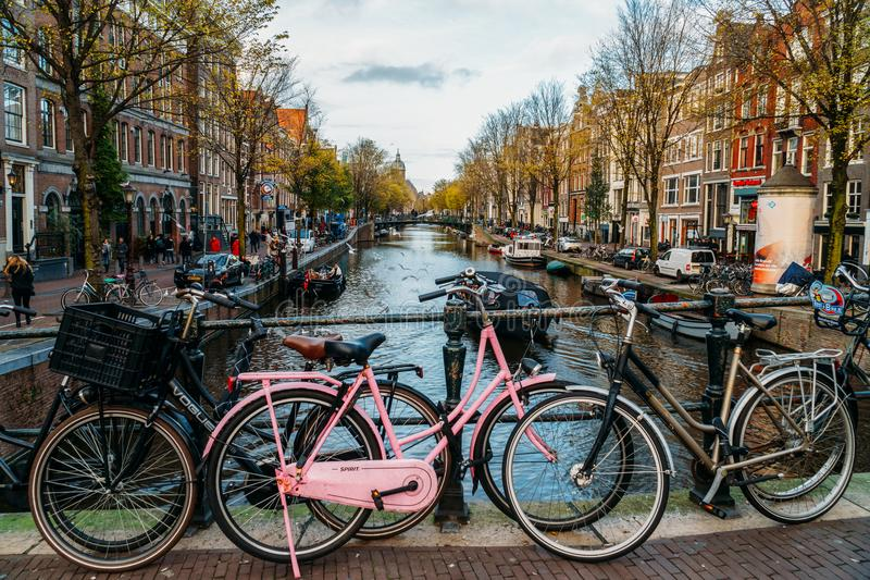 Bicycles and Dutch Houses On Amsterdam Canal In Autumn. AMSTERDAM, NETHERLANDS - NOVEMBER 13, 2017: Bicycles and Dutch Houses On Amsterdam Canal In Autumn stock image