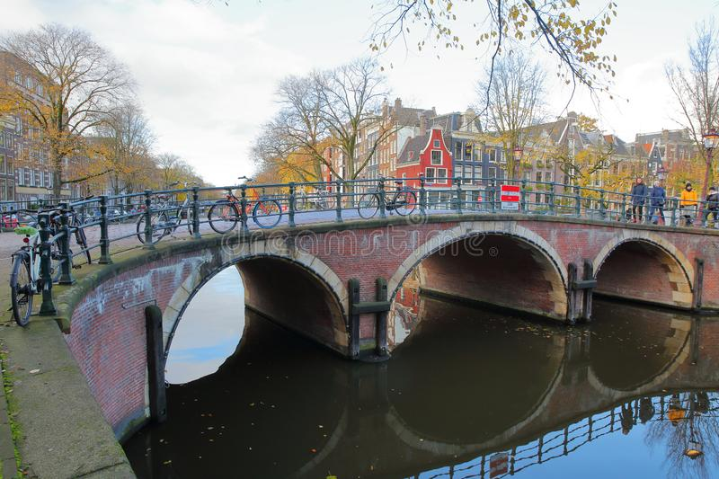 The junction between Prinsengracht Canal and Reguliersgracht Canal, with reflections of a heritage bridge and Autumn colors. AMSTERDAM, NETHERLANDS - NOVEMBER 19 royalty free stock images