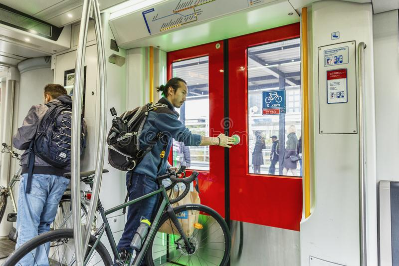 Amsterdam, Netherlands, 10/12/2019: People in a subway car. A man with a bicycle goes to the station royalty free stock image