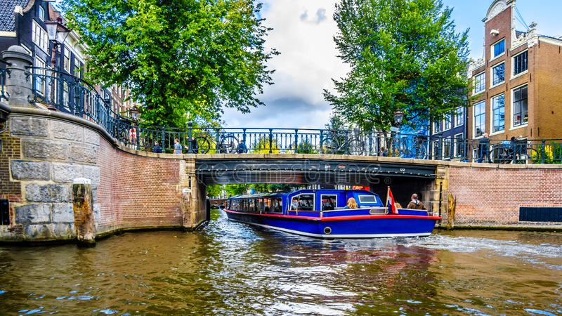 Canal boat under a bridge entering the Leidsegracht Leids Canal from the Prinsengracht Prince Canal in the center of Amsterdam. Amsterdam, the Netherlands - Sept stock images