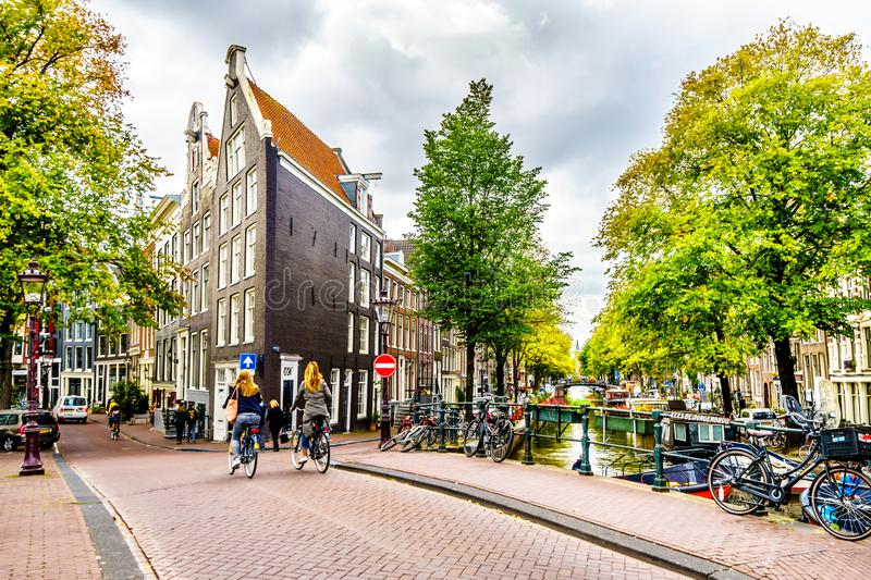 Locals biking over a canal bridge in the Jordaan neighborhood of Amsterdam royalty free stock images