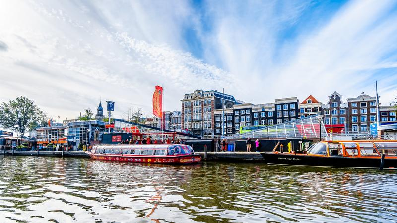 Tourist canal boats in the Damrak canal in the historic center of Amsterdam stock images