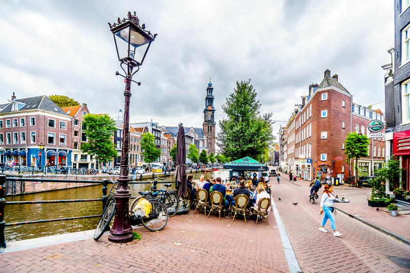 Typical scene of a gathering of tourists and locals at a cafe at the Prinsengracht in Amsterdam. Amsterdam, the Netherlands - Sept 28, 2018: Typical scene of a stock photos