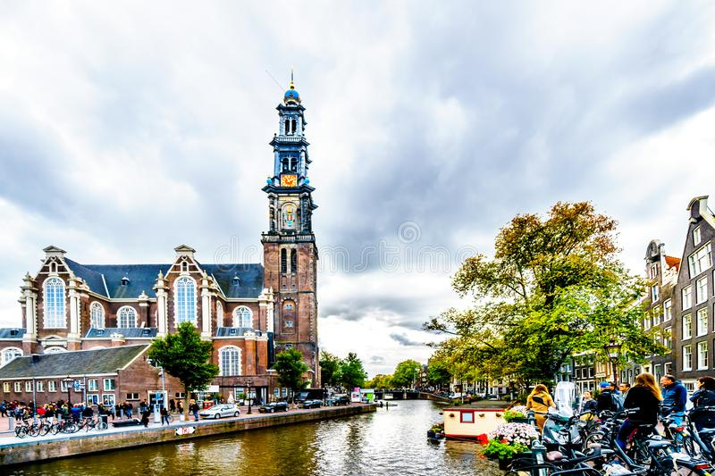 The Westerkerk church with the Westertoren tower seen from the Prinsengracht canals in the Jordaan neighborhood of Amsterdam. Amsterdam, the Netherlands - Sept royalty free stock photography