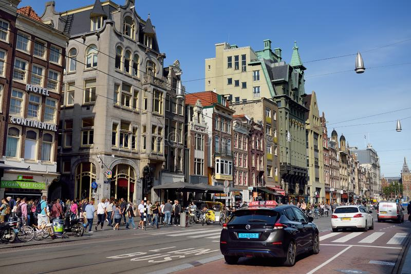 AMSTERDAM, NETHERLANDS - SEPTEMBER 17, 2018:Damrak central street of Amsterdam with tram, buildings and lots of people strolling royalty free stock images