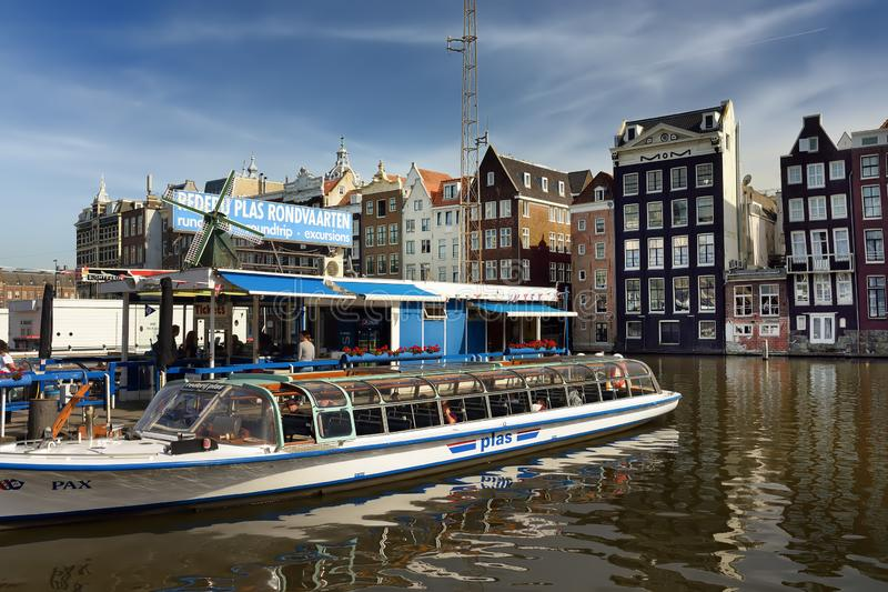 AMSTERDAM, NETHERLANDS - SEPTEMBER 17, 2018: Amsterdam`s famous dancing houses and river boat in the foreground on sunny summer royalty free stock photo