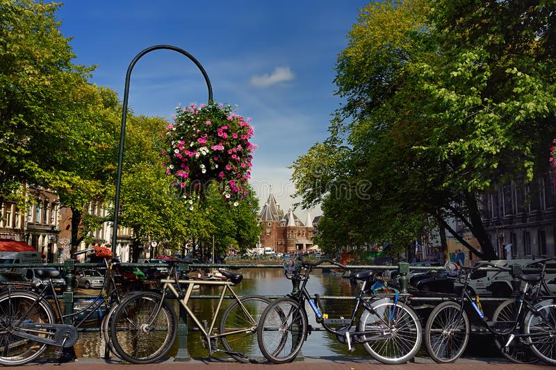 AMSTERDAM, NETHERLANDS - SEPTEMBER 17, 2018: Street, canal, bridge with bicycles, Nieuwmarkt New market building on background royalty free stock photography