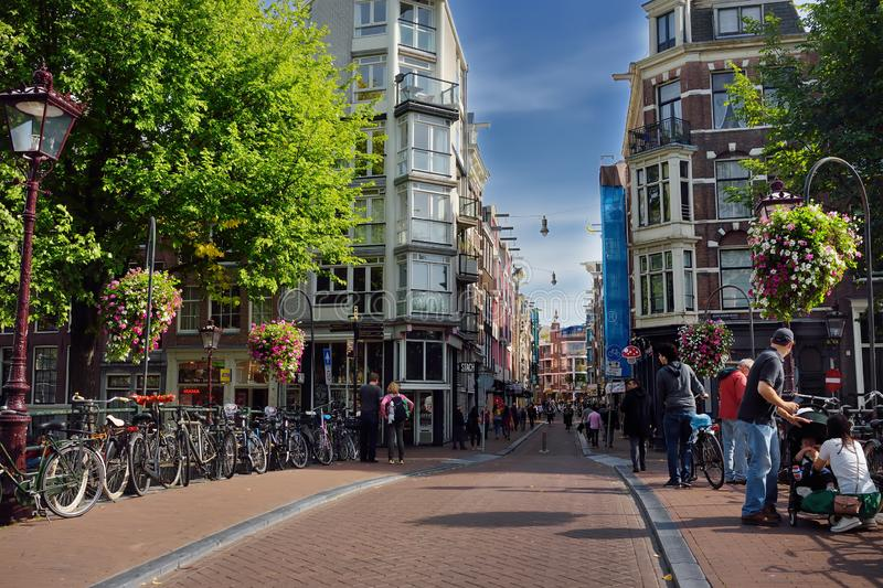 AMSTERDAM, NETHERLANDS - SEPTEMBER 17, 2018: Traditional view of street of Amsterdam with crowds of peoples, parking bicycles, stock images