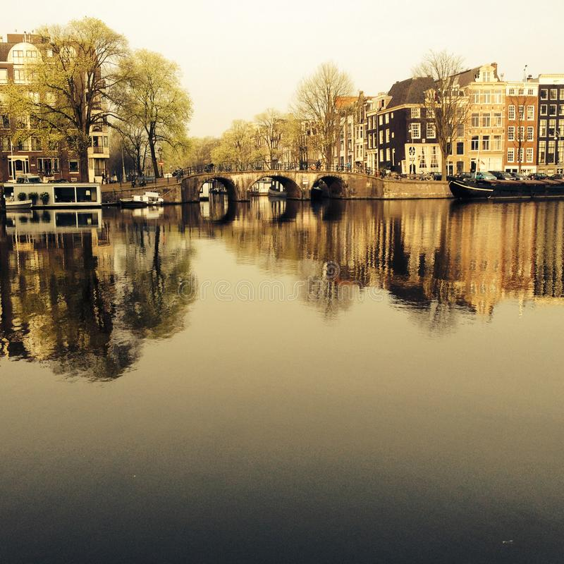 Amsterdam/THE NETHERLANDS: A typical view of the Amstel canal with old mansions in the center of Amsterdam, the N royalty free stock images