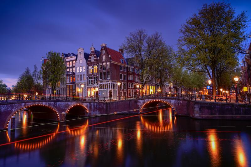Amsterdam by night with floating boats on the river canal , evening time , travelling to Netherlands. Europa royalty free stock photography