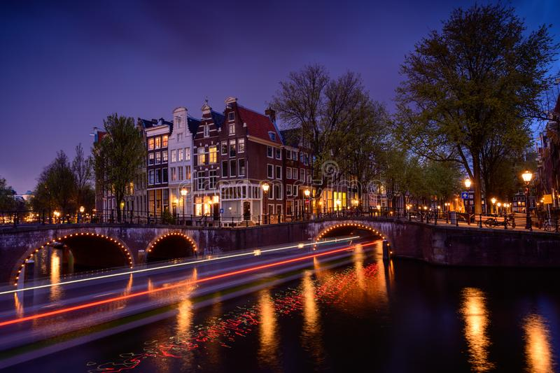 Amsterdam by night with floating boats on the river canal , evening time , travelling to Netherlands. Europa royalty free stock images