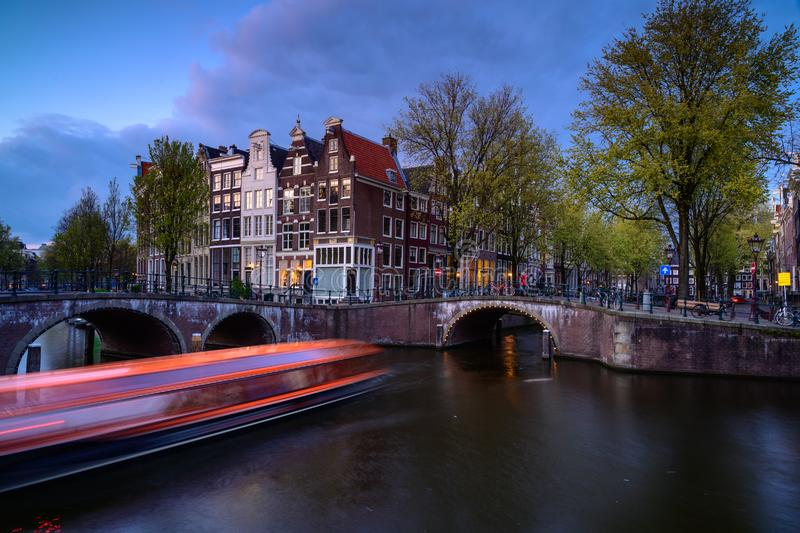 Amsterdam by night with floating boats on the river canal , evening time , travelling to Netherlands. Europa stock image