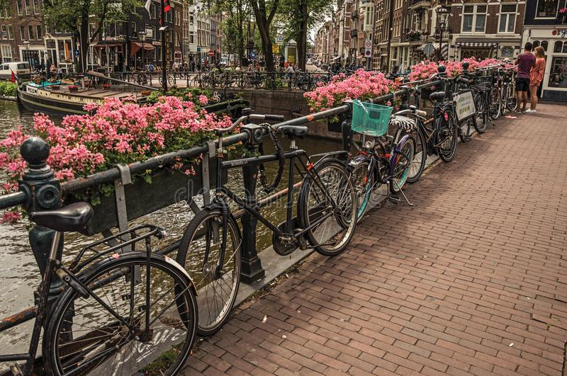 Bridge over canal with flowers, bicycles, old buildings and people in Amsterdam. stock photos