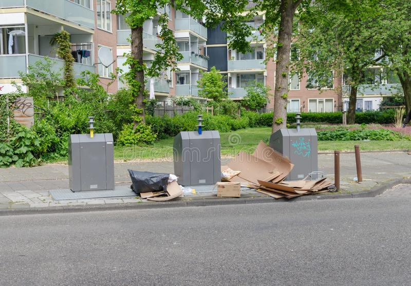 Amsterdam Oost. East side neighbourhoods. View of three garbage containers  for segregation with big carton near it. Street. Contamination. Copyspace stock photography