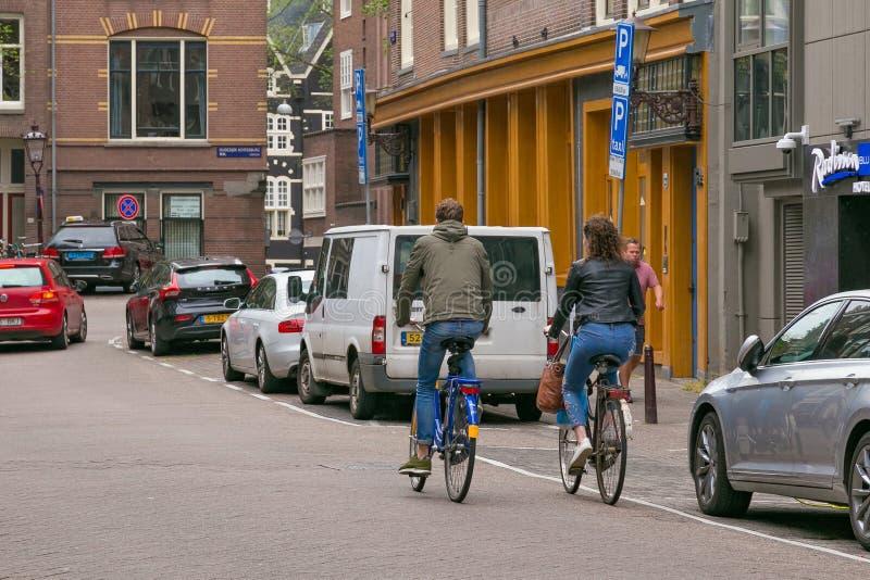 AMSTERDAM, PAÍSES BAJOS - 25 DE JUNIO DE 2017: Ciclistas desconocidos en una de las calles centrales foto de archivo libre de regalías