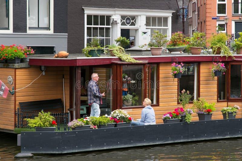 AMSTERDAM, PAÍSES BAJOS - 25 DE JUNIO DE 2017: Personas mayores desconocidas cerca de uno de los canales del agua en el centro hi imágenes de archivo libres de regalías