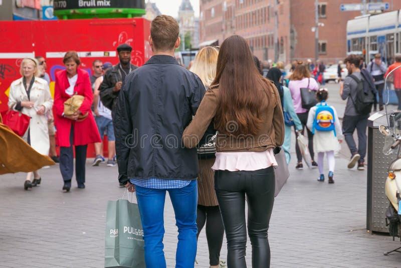 AMSTERDAM, PAÍSES BAJOS - 25 DE JUNIO DE 2017: Un par joven desconocido que camina una de las calles en el centro imágenes de archivo libres de regalías