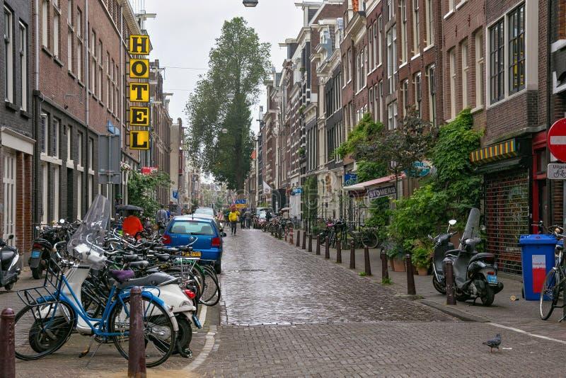 AMSTERDAM, PAÍSES BAJOS - 25 DE JUNIO DE 2017: Vista a la que está de la calle de la ciudad debajo de la lluvia en la parte histó fotos de archivo libres de regalías