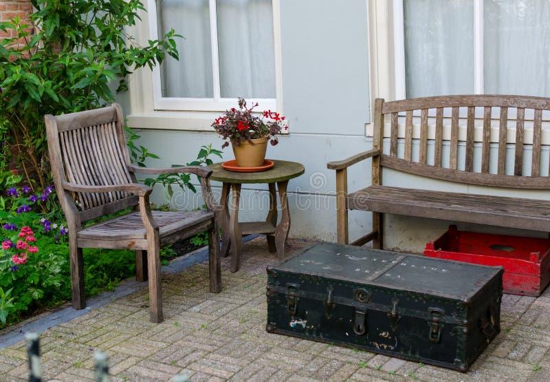 Amsterdam, Países Bajos - 4 de mayo de 2019: Diseño simple del patio trasero Muebles de madera viejos y siutcase negro del vintag fotografía de archivo