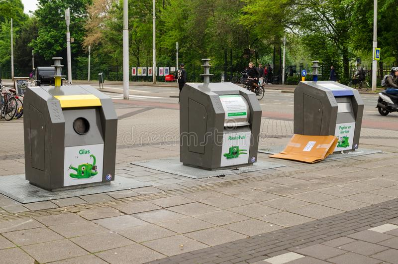 Amsterdam, Países Bajos - 3 de mayo de 2019: Tres envases de la basura para la segregación en la calle imagen de archivo libre de regalías