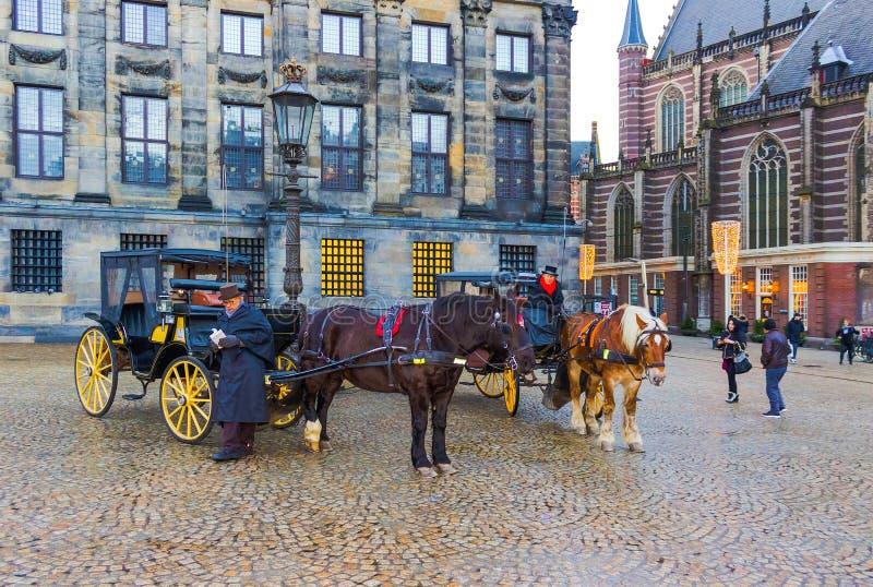 Amsterdam, Paesi Bassi - 14 dicembre 2017: Vista di un trasporto con i cavalli ed i monumenti storici a Amsterdam fotografie stock