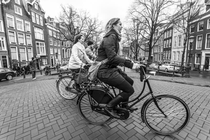 Amsterdam, Paesi Bassi - 26 febbraio 2010: Giovani donne che guidano sulle biciclette sulla via di Amsterdam fotografia stock