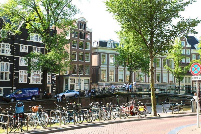 AMSTERDAM, PAESI BASSI - 6 GIUGNO 2018: bella vista dei canali di Amsterdam con le bici parcheggiate, la gente sul ponte fotografie stock libere da diritti
