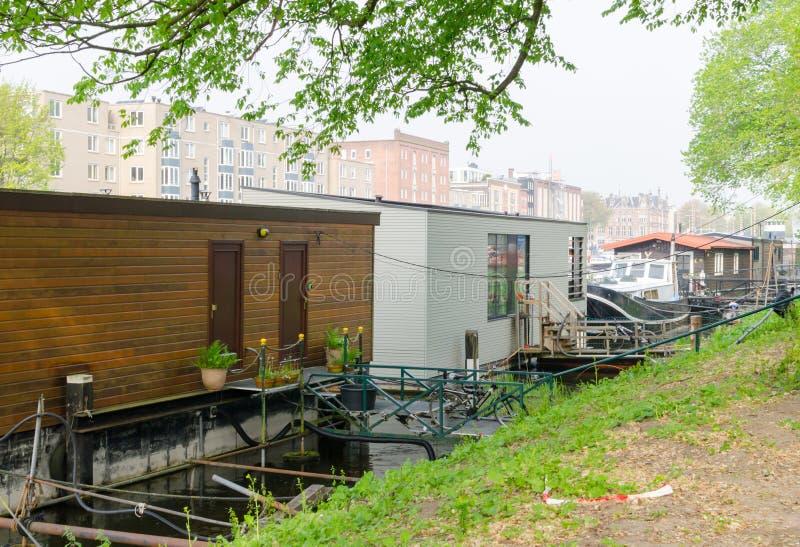 Amsterdam, Paesi Bassi - 3 maggio 2019 Case galleggianti sul canale di fiume Vivendo sull'acqua a Amsterdam fotografia stock libera da diritti