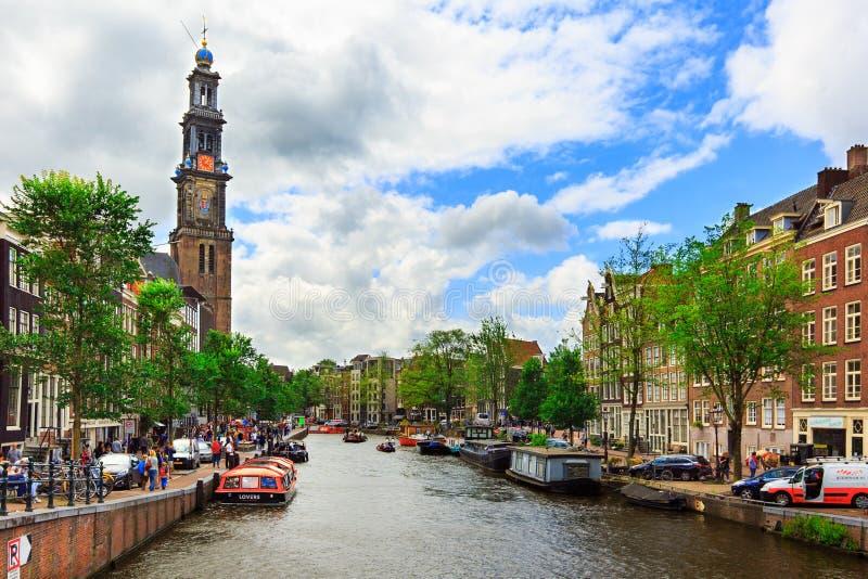 Amsterdam, Pays-Bas - 3 août 2017 : Maisons de la Hollande, église de Westerkerk, bateaux et personnes traditionnels sur le canal photographie stock libre de droits