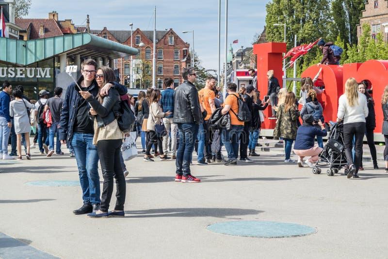 Amsterdam, Pays-Bas - 31 avril 2017 : Couplez prendre des selfies tandis que les gens marchant autour des lettres d'I Amsterdam d photographie stock libre de droits