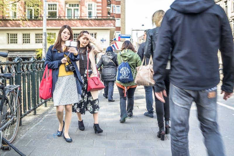Amsterdam, Pays-Bas - 31 avril 2017 : Touristes prenant des selfies tandis que les gens marchant autour dans les rues images libres de droits