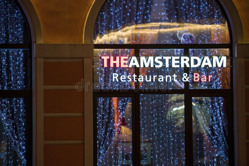 The Amsterdam Restaurant and Bar exterior in Rosa Khutor ski resort with neon sign and festive interior seen through transparent w royalty free stock photography